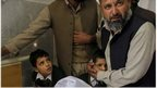 A Pakistani man comforts a student standing at the bedside of a boy who was injured in a Taliban attack on a school in Peshawar, Pakistan, Tuesday, December 16, 2014