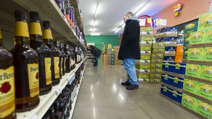 People looking at alcohol on the shelves in a shop