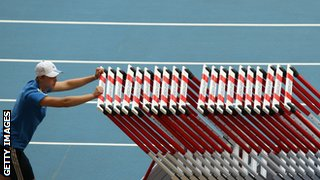 man pushing a stack of hurdles along an athletics track