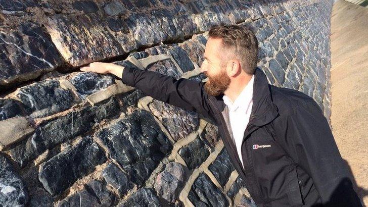 Man pokes hand in Dawlish sea wall