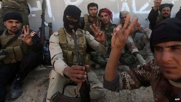 Shia militiamen from the Popular Mobilisation make victory signs while taking part in an Iraqi government offensive to recapture Tikrit (11 March 2015)