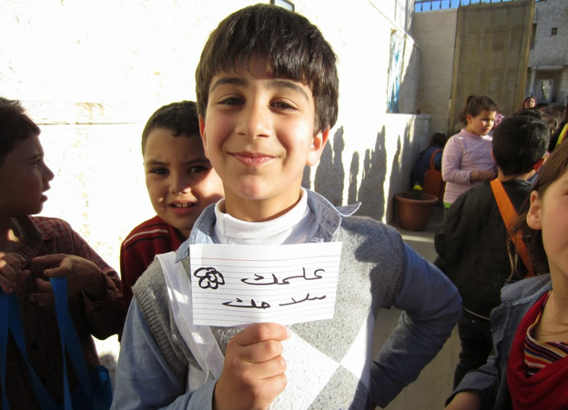 "Boy holding card ""Education is your weapon"""