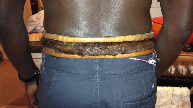 Back of man wearing elaborate belt or gris-gris