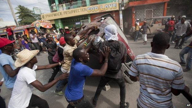 Demonstrators flip a car to block off a street during a protest demanding the resignation of President Michel Martelly in Port-au-Prince, Haiti
