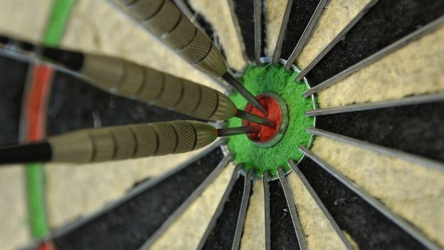 Three darts in the bullseye of a dart board