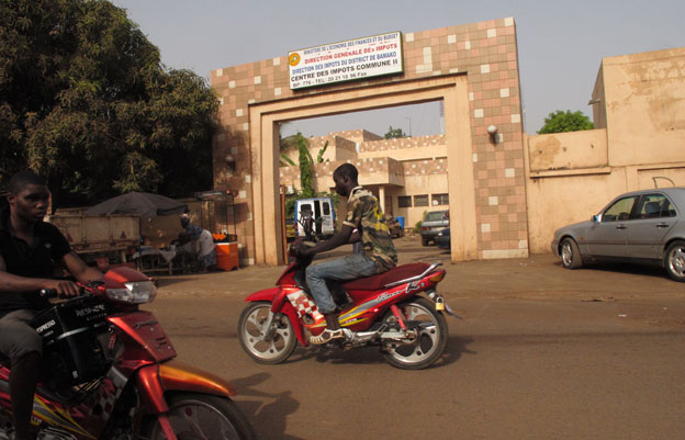 Motorbikes driving past the tax office in Bamako