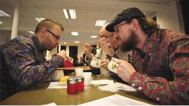 Three men enjoying soup