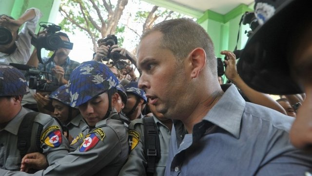 Philip Blackwood is escorted by Myanmar policemen as he comes out from court after being sentenced to two and a half years in prison in Yangon, Myanmar