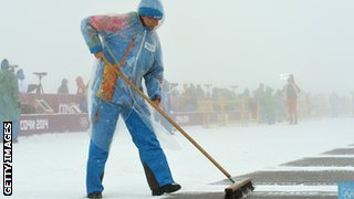 volunteer in the snow sweeping the course