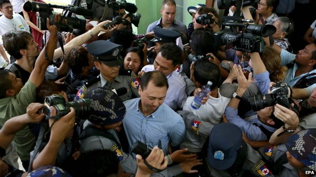 Tun Thurein (centre) is escorted by policemen along with Htut Ko Ko Lwin, and Philip Blackwood after being sentenced two and a half years in prison by a court, (17 March 2015)