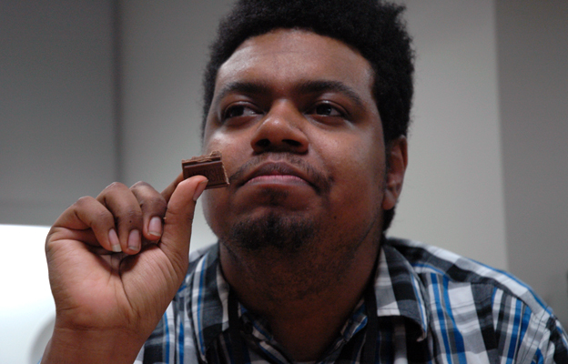Ishmael Buckner holds a piece of chocolate, preparing to taste it. He has a thoughtful look on his face.
