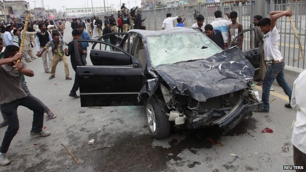 Protesters from the Christian community attack a car during clashes with riot police
