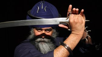 Nidar Singh Nihang the last living master of Shastar Vidiya, holds a sword in front of his face.