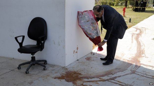 Souheil Alouini, a member of Tunisian parliament lays flowers next to a a blood stain at the Bardo museum in Tunis, Thursday, March 19, 2015