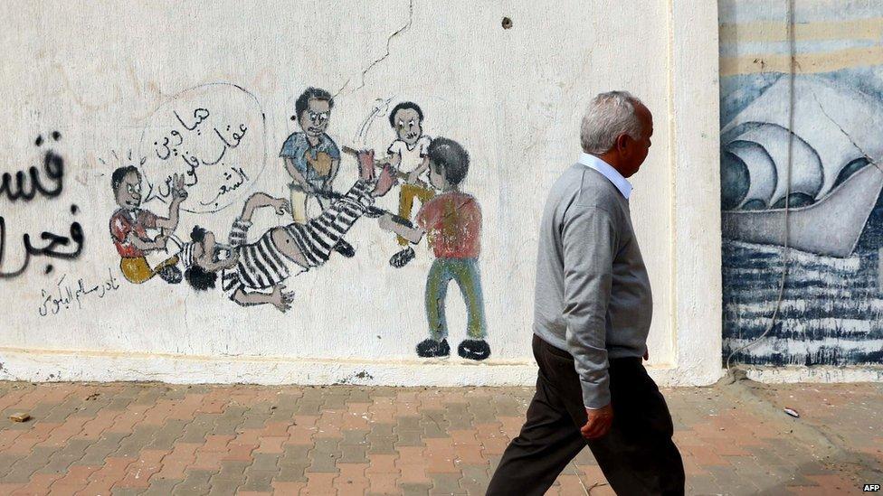 A Libyan man walks past graffiti depicting Libya's killed leader Muammar Gaddafi being tortured in the capital, Tripoli, on 17 March 2015