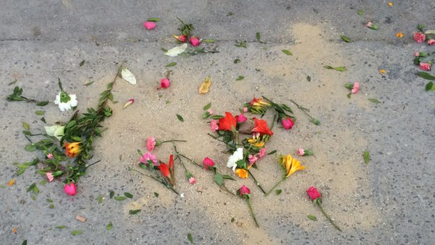 Flowers on ground as memorial to victims