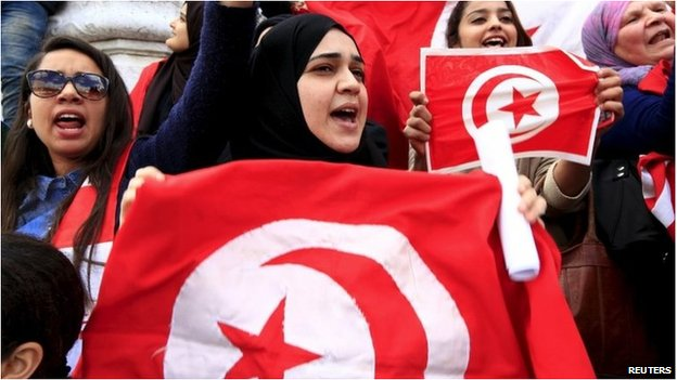 Tunisian protesters shout slogans as they wave banners and their national flag during a demonstration on independence day in Tunis  - 20 March 2015