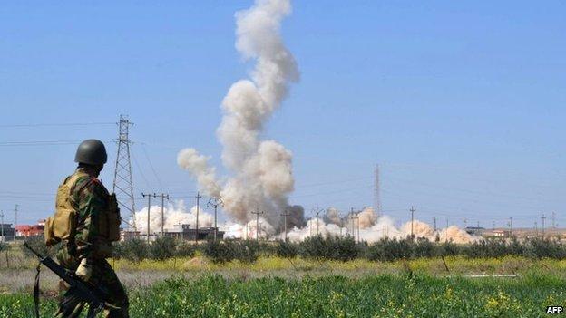 An Iraqi Kurdish Peshmerga soldiers looks on as smoke rises following an explosion east of Kirkuk (10 March 2015)