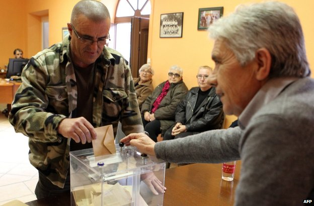 A man casts his ballot during the first round of the French departmental elections on 22 March 2015 in Corsica