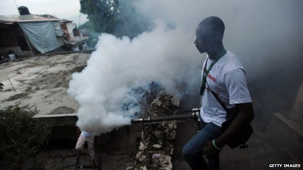 A worker from Haiti's Ministry of Public Health sprays chemical to exterminate mosquitoes in a neighbourhood of Petion Ville in Port-au-Prince on 21 May, 2014