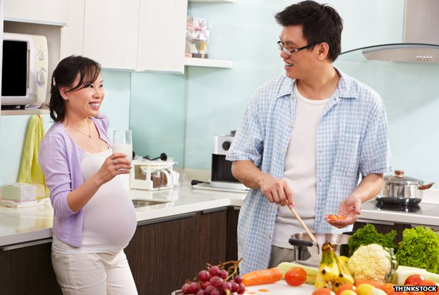 A pregnant woman and a man preparing food
