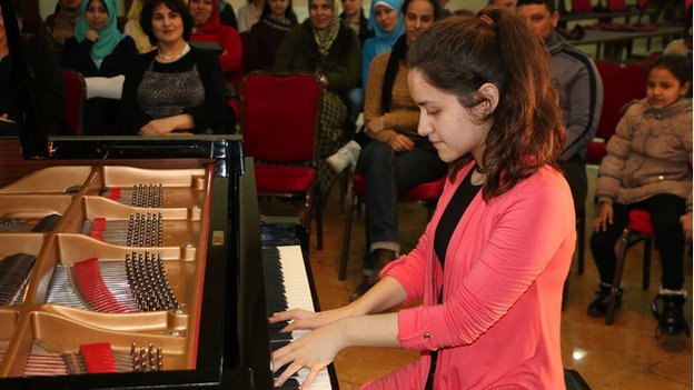 A girl playing a grand piano at a concert