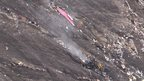 A screen grab taken from an AFP TV video on 24 March 2015 shows debris of the Germanwings Airbus A320 at the crash site in the French Alps