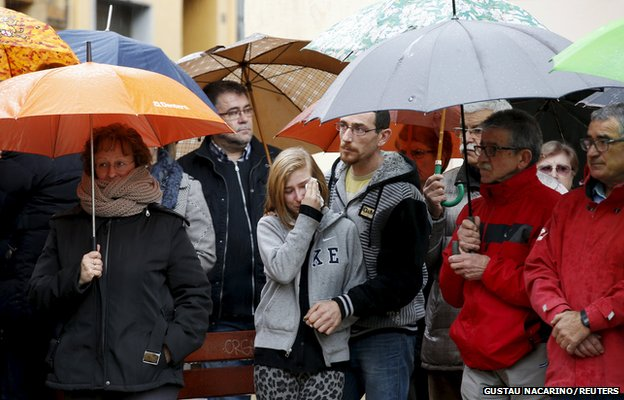 People react as they observe a minute of silence in Llinars del Valles, near Barcelona