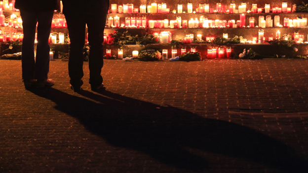 Pupils stand in front of candles and flowers that have been left outside the Joseph-Koenig college in Haltern am See, Germany, 24 March 2015.