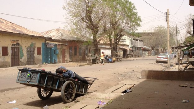 A man asleep on a cart in Sabon Gari, Kano, Nigeria