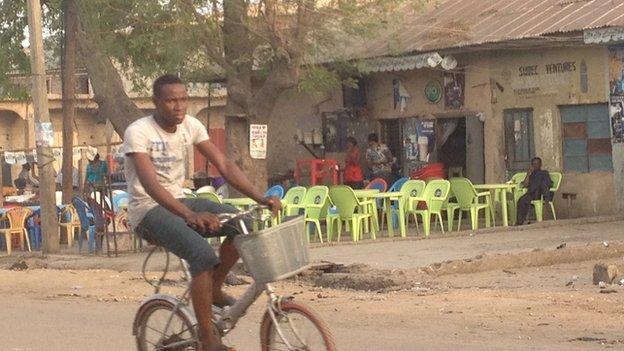 A man riding a bicycle past a bar in Sabon Gari in Kano, Nigeria