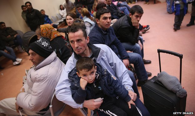 Migrants wait to register at the Central Registration Office for Asylum Seekers in Berlin on 11 March 2015