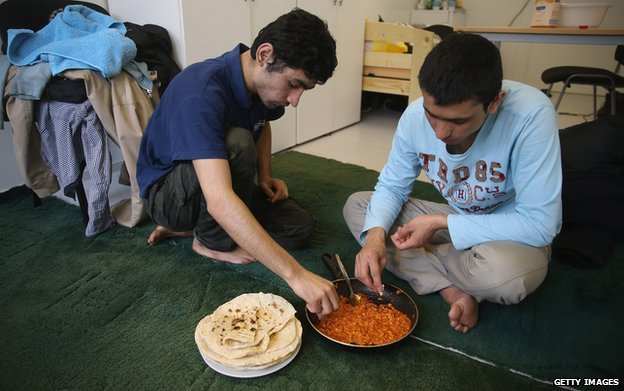 Cousins from Afghanistan eat lunch at a container settlement for refugees in the Allende quarter of Koepenick district on 6 March 2015 in Berlin, Germany