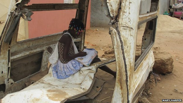 Child doing homework in wreck of car