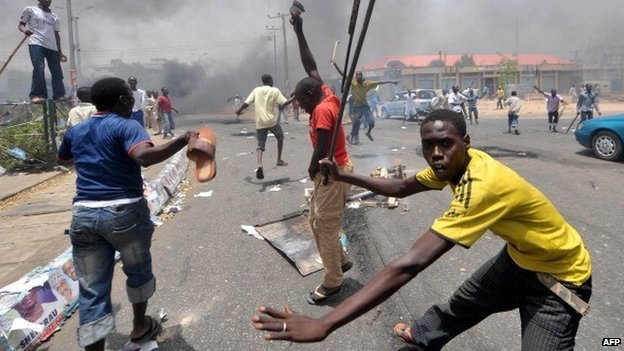 People holding wooden and metal sticks demonstrate in Nigeria's northern city of Kano where running battles broke out between protesters and soldiers on 18 April 2011 as President Goodluck Jonathan headed for an election win