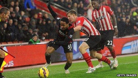 Matt Targett (stripes) of Southampton tussles with Raheem Sterling of Liverpool