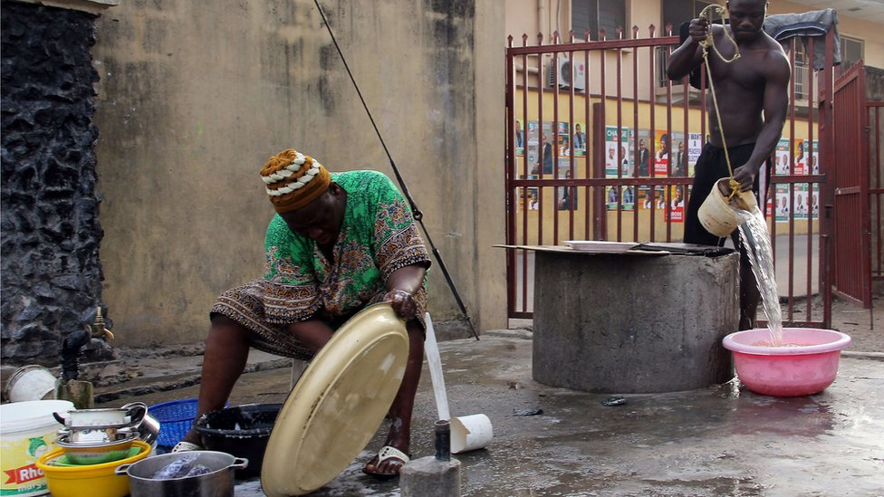 A Nigerian man fetches water from a well as a woman washes the dishes in Lagos on 19 March 2015