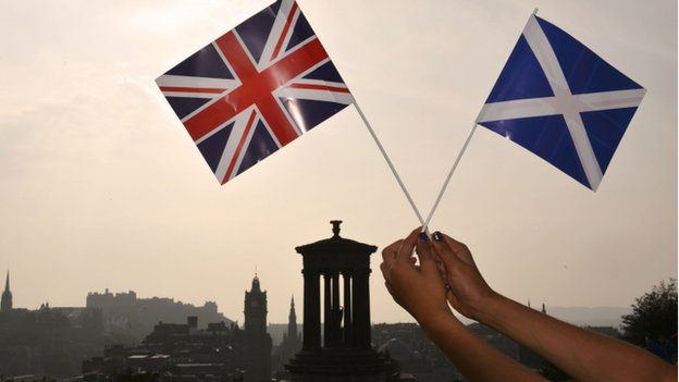 The Union Jack and Saltire held up in front of the Edinburgh skyline