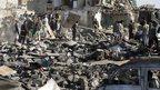 People looking through wreckage