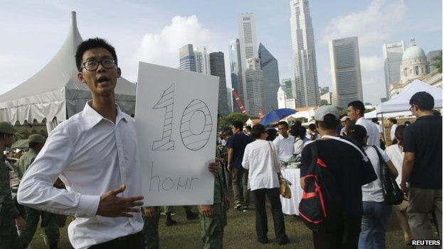 A man holds a sign with the estimated queue time in Singapore (27 March 2015)