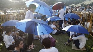 People wait under umbrellas near Parliament House (27 March 2015)