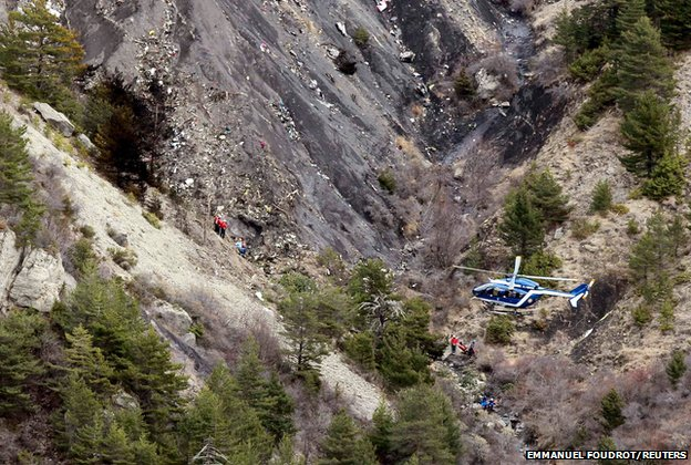 A French gendarme helicopter flies over the mountain-side crash site