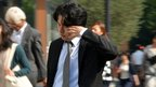 A Japanese worker rubbing his eyes while crossing a road on the way to work