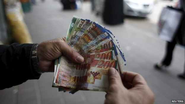A Palestinian money exchanger holds money at a market in the West Bank city of Ramallah (25 March 2015)
