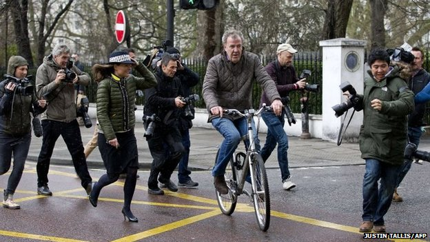 British television presenter Jeremy Clarkson leaves his home on a bicycle in west London