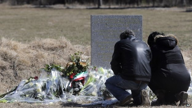 Family members of a victim kneel by a plaque and flowers laid in memory of the victims near the area where the Germanwings jetliner crashed in the French Alps, in Le Vernet, France, Friday, March 27, 2015