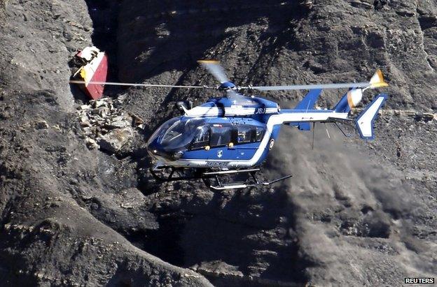 A French police helicopter flies over the crash site in the Alps, 27 March