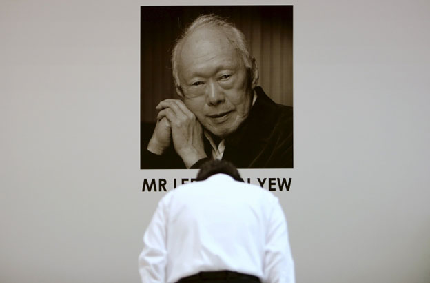 Man bowing before photograph of the late Lee Kuan Yew