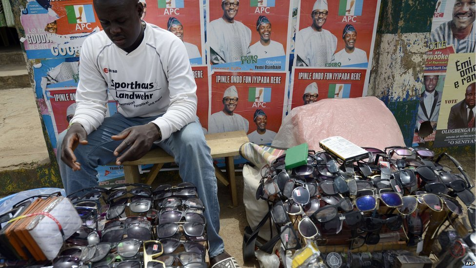 A vendor sells sunglasses at his roadside shop in front of posters of the main opposition All Progressives Congress (APC) presidential candidate Mohammadu Buhari and running mate Yemi Osinbajo in downtown Akure, Ondo State south-western Nigeria, on 23 March 2015