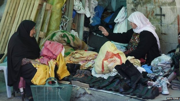 A Palestinian woman sells second-hand clothes and shoes at a market in the West Bank city of Ramallah (25 March 2015)